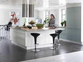 Det åpne kjøkkenet er holdt samme fargeskala som stuedelen, men materialvalget er annerledes. Gulvet er flislagt og flukter med eikegulvet.