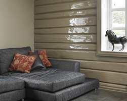 Tømmeret blir «fett» og lekkert i uttrykket med blank maling, her i farge S 5010-Y30R. Vindusomrammingen har fått samme behandling. Det blanke treverket fremheves ekstra av den matte veggen i farge S 4010-Y30R.