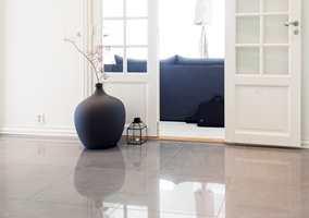 ROM PÅ ROM Fra hallen ser man inn i en av stuene, med samme veggfarge og mørke møbler. Den sorte krukken refererer til møblene, og blanke gulvfliser reflekterer lyset.