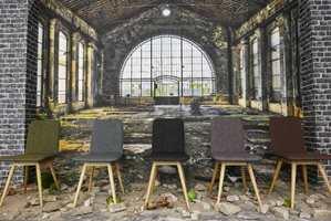 <b>KONTRASTER:</b> Men like fullt harmonisk. Enkle stoler i dempede naturfarger, myke tekstiler og lyst treverk mot en rå industrihall (fototapet). (Foto: Bjørg Owren/ifi.no)