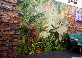 Fototapet med jungelmotiv, med papegøye, apekatt og tiger prydet Komars stand.