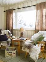 Gamle møbler mot nye farger. Her finner vi igjen grønnfargen fra dørene i gardiner og pute.
