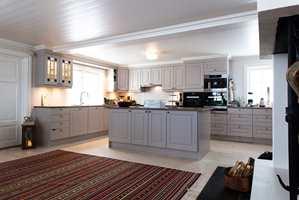 En drøm av et kjøkken; romslig, delikate farger, peis. Man kan nærmest fornemme duften av gjærbakst...