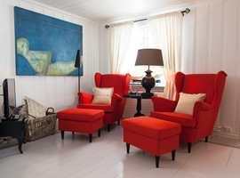 Denne stuen fungerer også som kontor. De oransje stolene og veggbildet står i spennende kontrast til hverandre. Legg merke til at gulvet er påført dekor langs veggene.