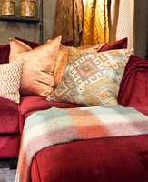 <b>HELMAKS</b> Oransje-kobber-gull-rødt-gult på en vinrød sofa. Alt fra Green Apple. (Foto: Chera Westman/ifi.no)