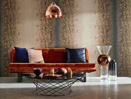 <b>HETT</b> Tapet fra Harlequin, med metallinnslag, samt lampe i kobber og velursofa står nydelig mot betonggulvet. (Foto: Tapethuset)
