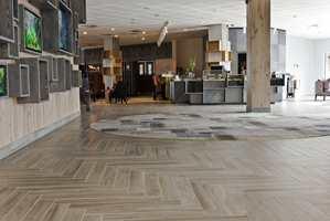 Entréen til hotellet er blitt storslått, med resepsjon, bar og restaurant til høyre. Hovedveggen er kledd med treparkett og dekorert med grå kasser som skal minne om drivved.