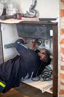 Rørlegger fra Rørkjøp kobler til vann på kjøkken