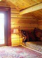 Hemsen har umalte vegger og tak men vinduskarmer, tepper og puter er fargerike innslag.