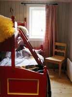 Soverommene har familiekøyer og enkel innredning. Panelet ved vindusveggen er malt grått og rutete gardiner gir en hyggelig atmosfære.