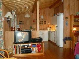 Kjøkken og spisekrok før. TV-en har måttet vike for en peisovn, som også fungerer som romdeler.