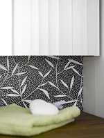 Mønsteret på våtromsvinylen gir rommet karakter, i fin kontrast til det hvitmalte panelet.