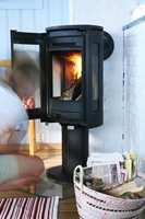 Ny ovn i fornyede omgivelser; hvitmalt brannmur og svale, blå vegger. De nå synlige flammene bidrar godt til atmosfæren.