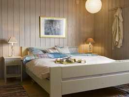 Upraktiske kommoder vek plassen for nette nattbord, som er malt i en lys, varm gråfarge, mens sengen er holdt i dus grønn.