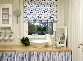 Hyttas minste soverom har blitt et tiltalende bad, med en lang benk som gir mye oppbevaringsplass – godt skjult bak forhenget. Tekstilene har samme farger i ulike mønster, fint avstemt mot de dusgrønne veggene.