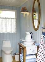 Toalettrommet har fått sin kjølige blåfarge fra himmelen, og innslag av gyllent treverk gjør rommet lunt og hyggelig.