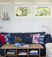 Veggfargen er lekker mot den blå sofaen, som for øvrig fikk et friskere uttrykk da de gule rammene ble borte. Hvitmalte vinduer reflekterer dessuten mer lys enn ubehandlede.