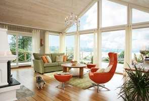 Hvilken luksus! De store glassflatene bringer verden utenfor inn, og gir samtidig en opplevelse av at stuen befinner seg ute. Til tross for alt lyset som flommer inn råder en lun atmosfære. Takhøyden, de store vinduene og den luftige møbleringen gir en enrom romfølelse. Gulvets gylne farger tilfører rommet varme og tyngde.