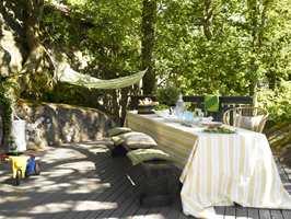 En stor, hyggelig terrasse, hvor gulvet (Butinox Terrassebeis, farge grå) har fått sin farge fra fjellet som omkranser den. Frodige trær kaster kjærkommen skygge over bord og benker.