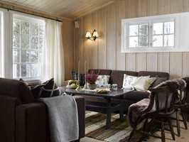 Brune sofaer byttet plass med den røde hjørnesofaen, og bordet er helt ugjenkjennelig i sin nye, mørkegrå drakt. Veggene skaper rolige rammer.