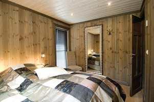 Panelet i hyttas soverom kommer enda mer til sin rett med beis: fargen heter