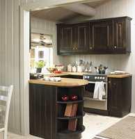 Kjøkkeninnredingen som stod i hytta var forholdsvis ny, og la grunnlaget for fargevalget. Benkeplaten ble imidlertid frisket opp med en gråtonet olje, og den hvite komfyren ble byttet ut med en mer dempet modell i stål.
