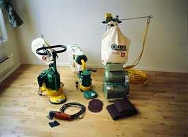 Utstyrspakken fra IBG på det gamle lakkerte gulv til slipeoppgaven på stuegulvet som senere skal oljes: Gulvslipemaskin, kantslipemaskin, trekantsliper til hjørner og diverse slipepapir.