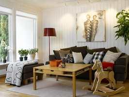 Lun stue: Naturskalaen fra sand til mørk kaffe gir stuen en lun atmosfære midt i alt det hvite. Maleriet er av Geir Stølen. Enkle, hvite rullgardiner tar vare på lys og kontakt ut.