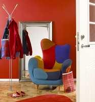 Inspirert av den fargerike stolen er hele entréen malt sterk rød. Siden dette ikke er noe oppholdsrom, tåles det mye farge. Dørene er hvite og roer ned. Teppet på gulvet er i samme rødfarge. Det er lett å se at det ville blitt kaos dersom vi hadde latt oss friste til å gjenta flere av fargene fra stolen. At det ble rødt er litt tilfeldig, for de andre fargene ville også vært gode.
