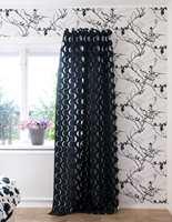 De halvt transparente tekstilene formidler overgangen fra lyst til mørkt. De er tredd på stang med maljer