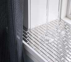 Vinduene har dype karmer med stålblanke mosaikkfliser. Materialet spiller raffinert sammen med gardiner i grov fibervev.