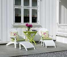 Siden skiferplattingen ble dratt rundt halve huset, kunne eierne også lage en liten uteplass i morgensolen. Her ble det brukt de samme fargene på møbler og tekstiler, noe som skaper helhet.