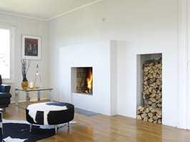 Den gamle peisen i stuen ble beholdt, men fikk en solid og moderne utforming med maling.