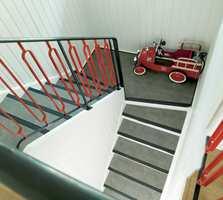 det originale smijernsgelenderet i trappen, som minnner om svunnen tid, overlevde oppussingen med stil. Malt med rød og sort metallmaling kom de elegante formene bedre frem.