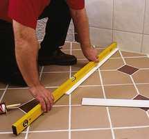 Start byggingen vinkelrett ut fra veggen og i vater fra gulvet. Lim plastlisten fast til gulvet.