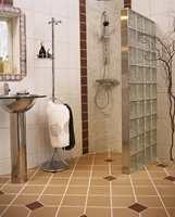 Veggen av glassbyggesten lager en romslig dusjnisje på badet.