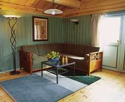 Før og etter: To deler av stuen som viser hvordan det naturlige treverket er malingbehandlet opp til overkant av vinduene.