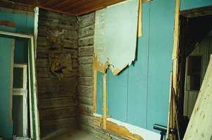Grunnkonstruksjonen i huset er i laftet tømmer som så er panelt med brede, håndhøvlede bord som heldigvis var i så god stand at de kunne pusses ned og males. For at det skulle kunne monteres peis her i midtstuen, måtte en kle inn hjørnet med brannmur.