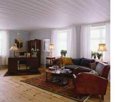 Storstuen går over hele den ene endeveggen. Her slipper lyset til fra tre kanter, og de lette gardinene i hvit bomullsvoile er ingen hindring. Med de lys grå veggene og det hvite taket slipper ingen gråværsdag til. Møblene med sitt varme treverk, det vakre gulvet og de flotte teppene skaper lunhet og hygge i rommet.