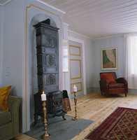 Den fantastiske etasjeovnen har fulgt huset lenge. Den ble flyttet ned fra et av soverommene og restaurert før den ble montert opp i ovnsnisjen i storstuen. Muren i nisjen er malt i samme gråtone som veggene og markert med en malt, okergul ramme. Veggfargen er den samme som i spisestuen, og på samme måte er dørene her malt i en mørkere nyanse med rammer i okergult.