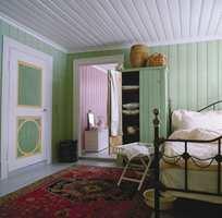 Fra dette rommet er det gjennomgang til neste soverom, og fargene må derfor harmonere. En praktfull louis-seize-dør med karakteristiske, rillede speifyllinger står i kontrast til det enkelt bygde skapet som er malt i samme beroligende grønnfarge som veggene. Grønt er en klassisk soveromsfarge med tradisjoner. Et deilig teppe i orientalsk stil luner på det gråmalte tregulvet og smijernssengen er redd opp med romantisk sengetøy.
