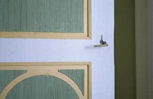 De rillede flatene i døren tar opp fargen på veggene i det grønne soverommet. Speilene aksentueres nydelig av en mild gul, mens hvitt ramtre markerer døren.