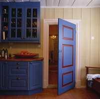Også på kjøkkenet er taket malt hvitt, det samme er listene, vinduene og geriktene. Dørene ble malt i den samme blåfargen som innredningen, med speilene rammet inn av en dyp rødfarge.
