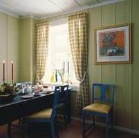 Til veggpanelet på kjøkkenet ble det valgt en gulhvit farge som nok kan ha et grønnskjær i noen lysforhold. Den skaper lunhet, er en god kontrast til den blå innredningen og henter opp toner fra den gule midtstuen og inngangspartiet.