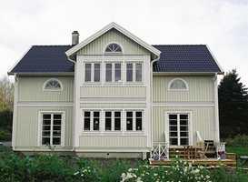 Huset er høyt og står på flat tomt, og derfor er det valgt en nøytral farge.