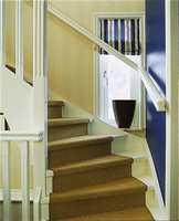Trappen fører opp til soverom, TV-stue og bad. Den er hvitmalt med en naturfarget løper i sisal .