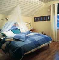 Et hvitpatinert tak og lyst og hvite gardiner gjør soverommet større. Sengen har pute- og dynetrekk av bomull og ekstra puter i damask.