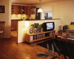 Moderne kjøkken og åpen stue. Halvveggen gjør rommene større samtidig som den skiller de.