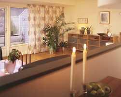 Bilde tatt fra kjøkkenet. Gardinpaneler skjuler den litt rotete vindusløsningen og gir en helhetlig løsning til rommet.