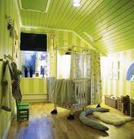 Et irrgrønt barnerom med detaljer i hvitt og blått. Stripene på veggen er malt.